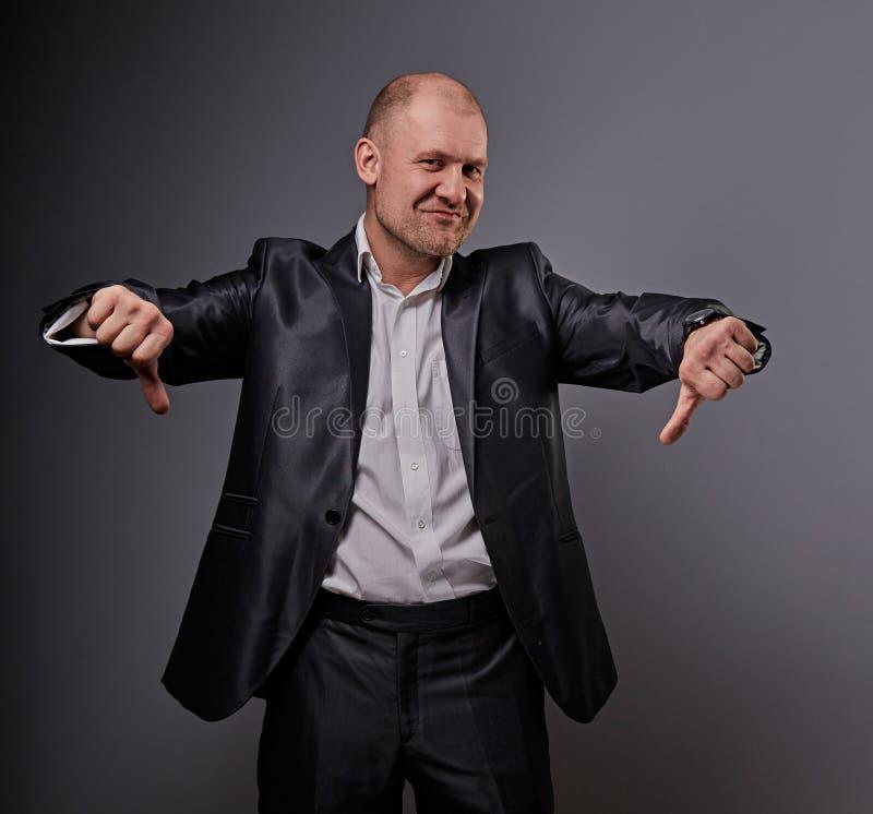 Zabawa komiczny łysy biznesowy mężczyzna w czarnym kostiumu pokazuje palcowego sukcesu kciuka puszka znaka na popielatym tle zbli fotografia stock