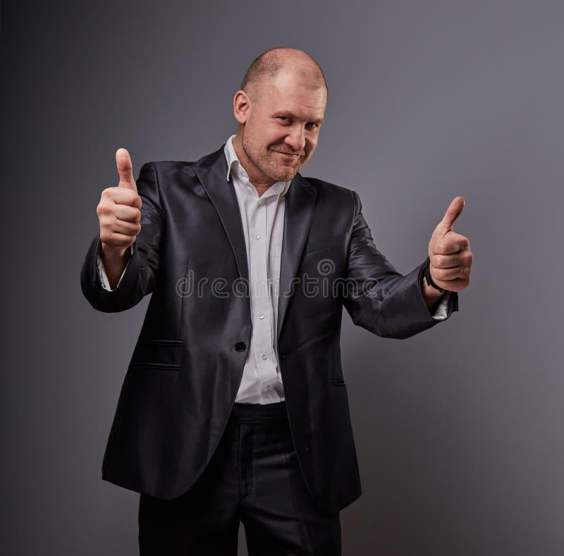 Zabawa komiczny ?ysy biznesowy m??czyzna w czarnym kostiumu pokazuje palcowego sukcesu kciuk w g?r? znaka na popielatym tle zbli? obrazy royalty free