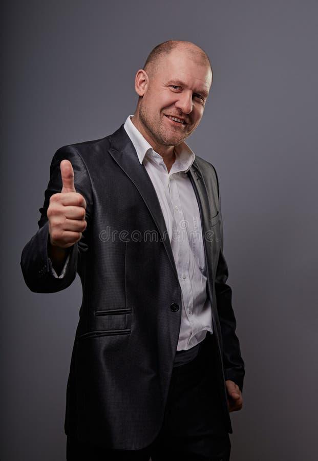 Zabawa komiczny ?ysy biznesowy m??czyzna w czarnym kostiumu pokazuje palcowego sukcesu kciuk w g?r? znaka na popielatym tle zbli? fotografia stock