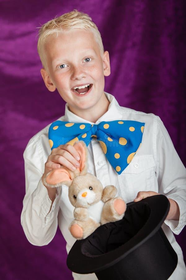 Zabawa młody magik ciągnie królika od odgórnego kapeluszu fotografia stock
