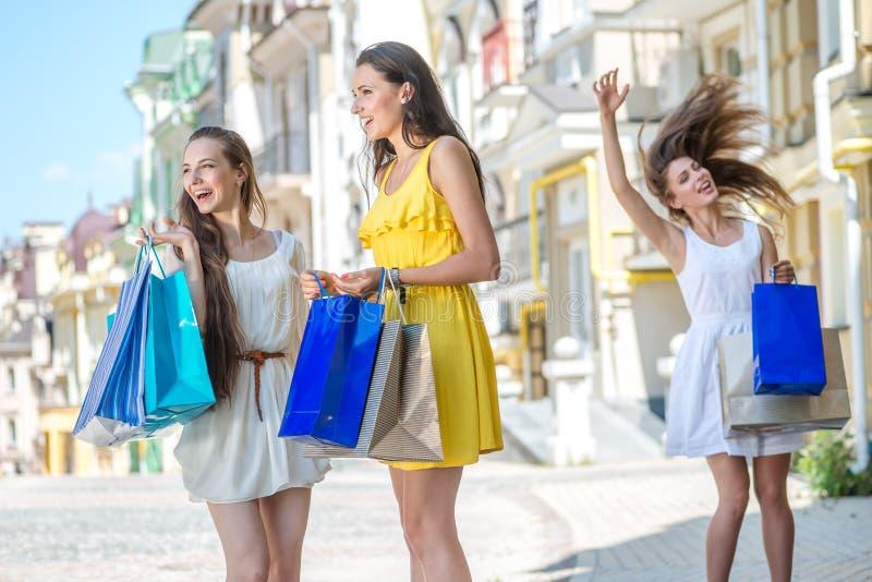 Zabawa zaczynał Trzy dziewczyny trzyma torba na zakupy i spacer wokoło obrazy royalty free