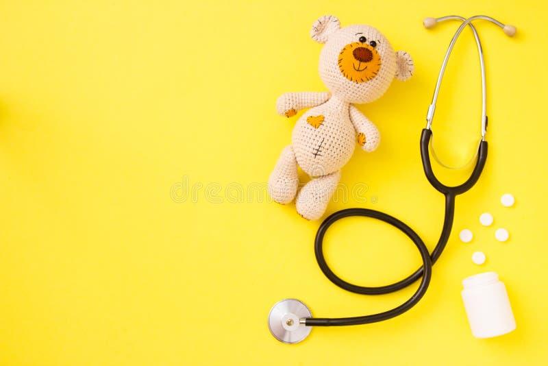 Zabawka dla dzieci miś amigurumi z stetoskopem na żółtym tle z przestrzenią kopiowania Koncepcja zdrowia dzieci Widok z góry, pła zdjęcie stock