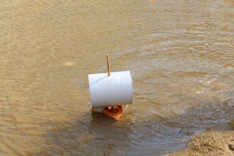 Zabawkarska drewniana łódź z żaglem papier unosi się wzdłuż fala brzeg na słonecznym dniu, zdjęcia royalty free