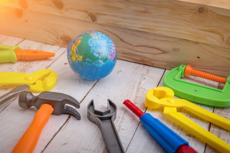 Zabawkarska kula ziemska i narzędzia przed drewno ścianą fotografia stock