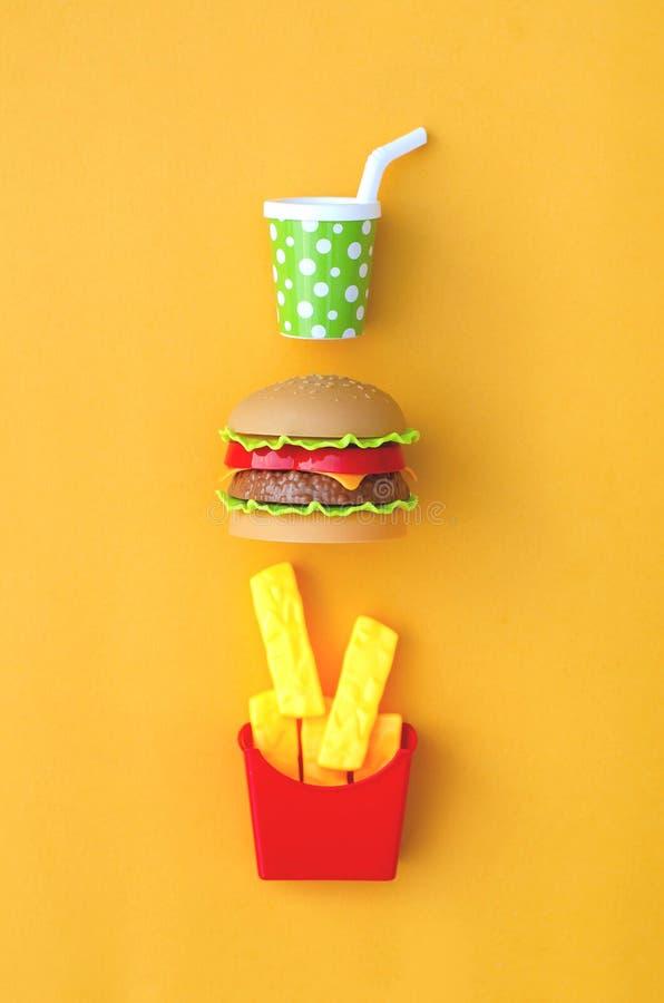 Zabawkarski fastfood jedzenie, napój na pomarańczowym tle i zdjęcie stock