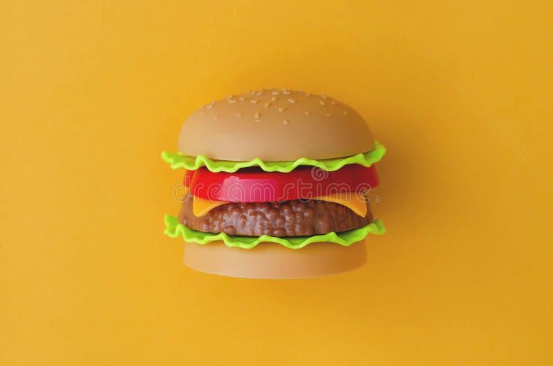 Zabawkarski hamburger z mięsem i sałatką na pomarańczowym tle obraz royalty free