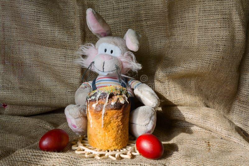 Zabawkarski królik, wielkanoc tort i kolorów jajka na stole, fotografia royalty free