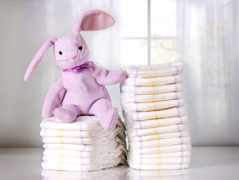 Zabawkarski królika obsiadanie na stercie rozporządzalne pieluszki lub pieluchach, sterta pieluszki, pampers zdjęcia royalty free