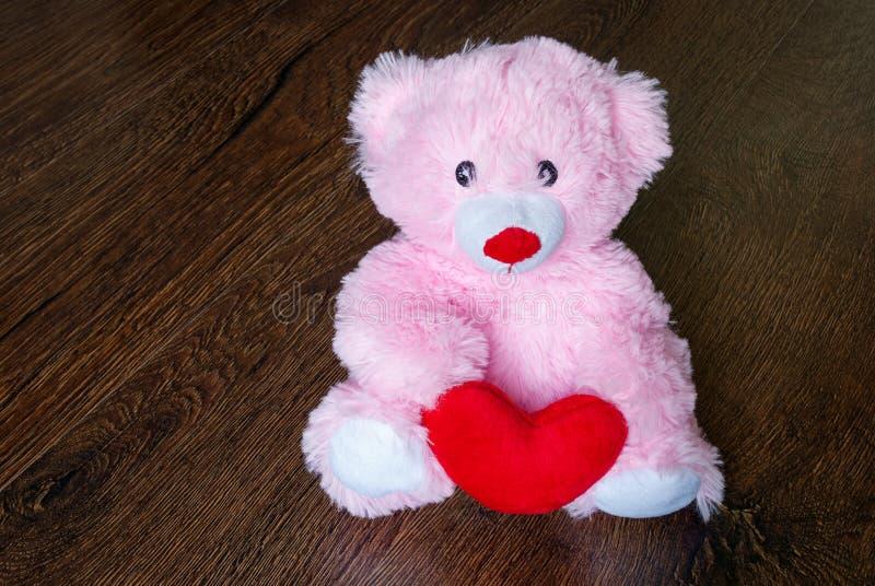 Zabawkarski miś pluszowy z sercem odizolowywającym na drewnianym tle zdjęcie royalty free