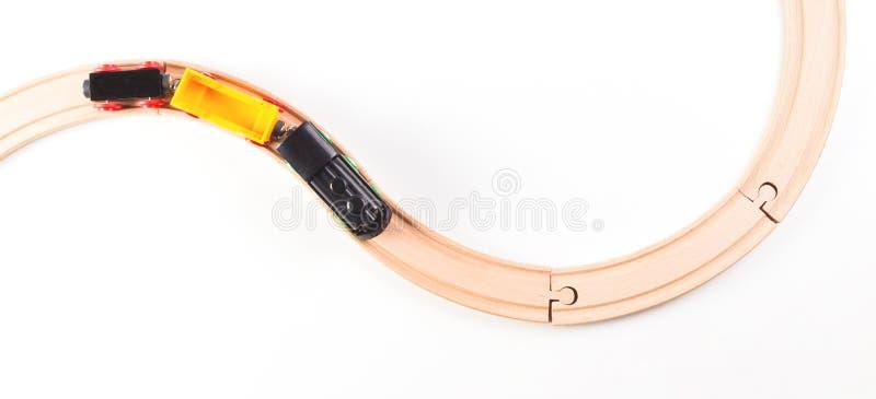 Zabawkarski pociąg z wyginać się drewnianymi kolejami na białym tle Odgórny widok zdjęcie royalty free