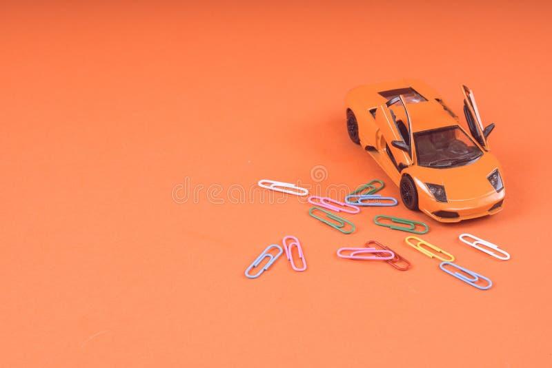 Zabawkarski pomarańczowy samochód na pomarańczowym tle, Sporta samochód w górę strzału, obrazy stock