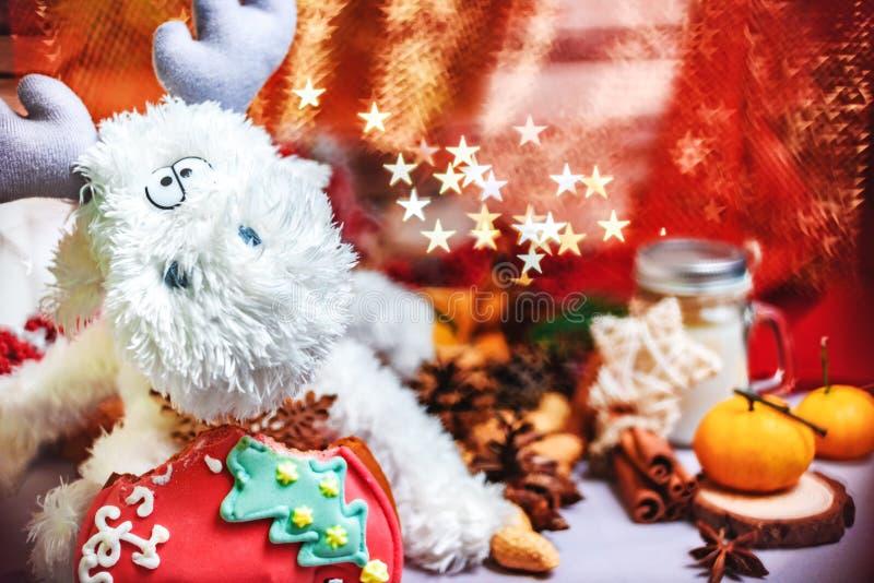 Zabawkarski renifer z gwiazdami w rękach, tangerins, ciastkach i jaskrawym gwiazdowym kształta bokeh, zdjęcie royalty free