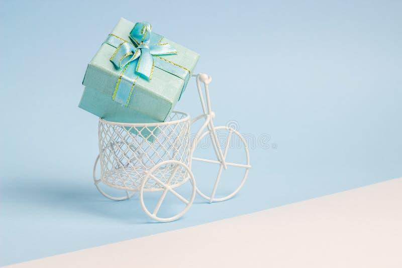 Zabawkarski rower niesie prezent Pomysł dla pocztówki niebieska t?a minimalista obrazy royalty free