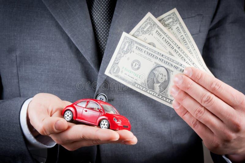 Zabawkarski samochód i dolary w rękach biznesowego mężczyzna pojęcie dla ubezpieczenia, kupienie, wynajmowanie, paliwo, usługa lub obraz royalty free