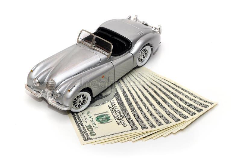 Zabawkarski samochód i pieniądze nad bielem Czynszu, zakupu lub ubezpieczenia pojęcie, fotografia stock