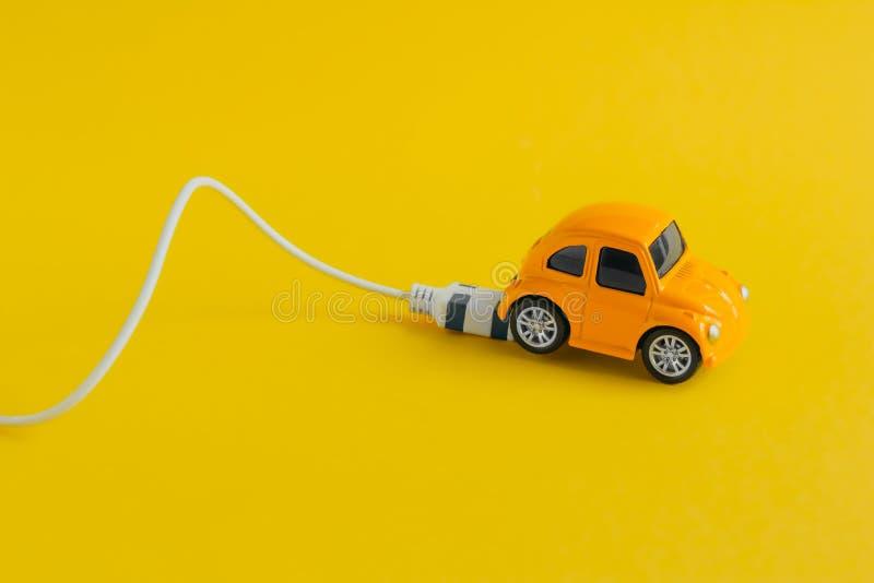 Zabawkarski samochód z ładuje kablem odizolowywającym na żółtym tle, elektrycznego samochodu pojęciu i życzliwym styl życia, zdjęcia stock
