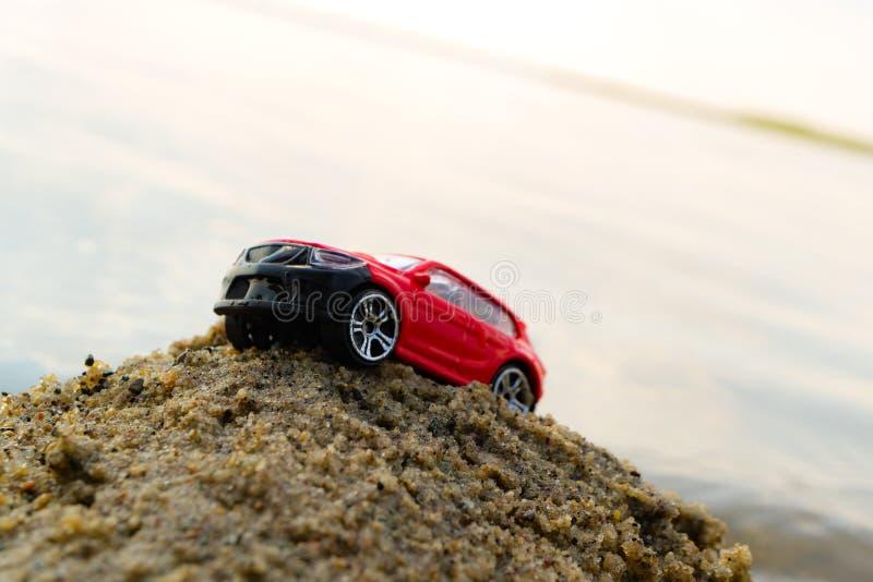 Zabawkarski samochodowy próbować wzywać stos piasek na plaży śmiecący horyzont w tle morze obrazy stock