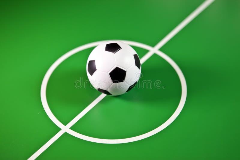 Zabawkarski soccerball w środku boiska w centrum zielony pole, zdjęcie stock