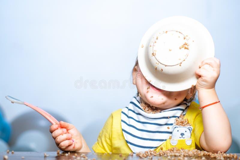 Zabawne jedzenie dziecka Małe dziecko jedzące obiad i robiące bałagan zdjęcia royalty free