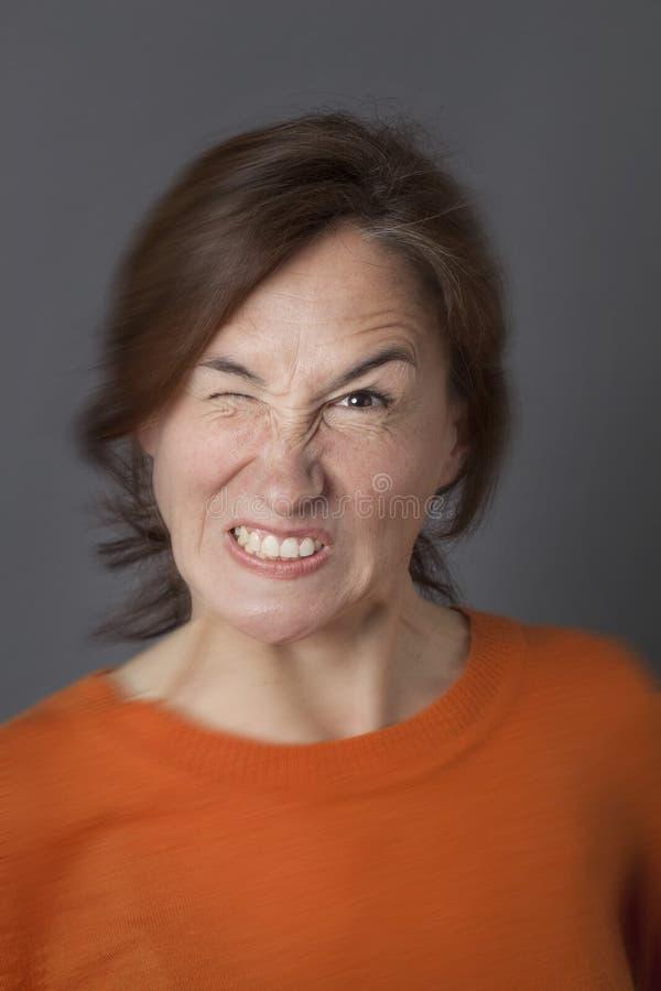 Zabawy gniewny wyrażenie dla mrugać w średnim wieku kobiety, plama skutki obrazy stock