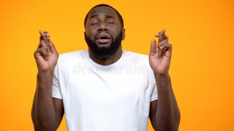 Zabobonny afroameryka?ski skrzy?owanie m??czyzny modlenia i palca szcz??cie na dobre zdjęcie stock
