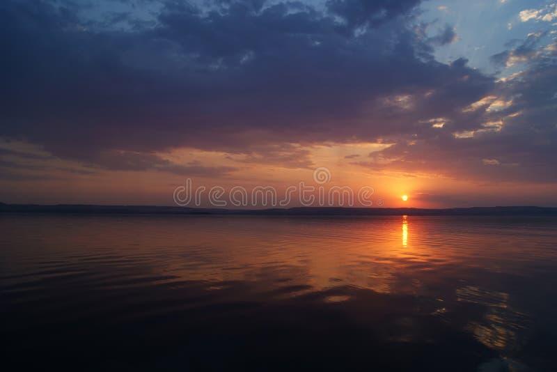 zachód słońca nad rzeką Słońce w chmurach siedzi przez rzekę zdjęcie stock