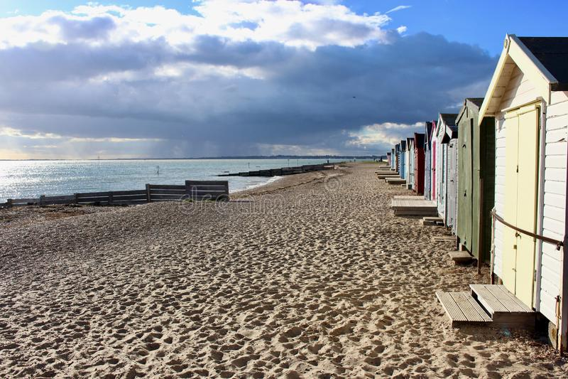 Zachodnia Mersea plaża z plażowymi budami i ciemny grożenie chmurniejemy obraz royalty free