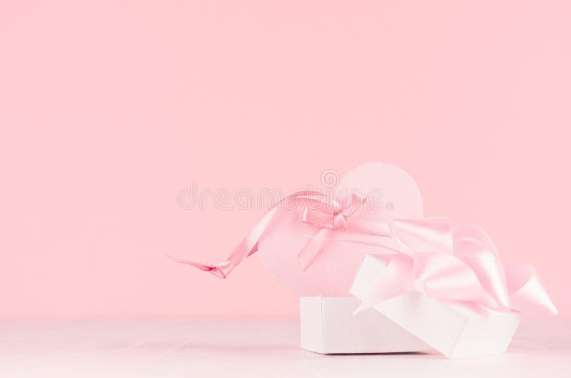 Zacht decor voor Valentine-dagen - zacht lichtrose hart met lint en huidig vakje op witte houten raad, exemplaarruimte stock fotografie
