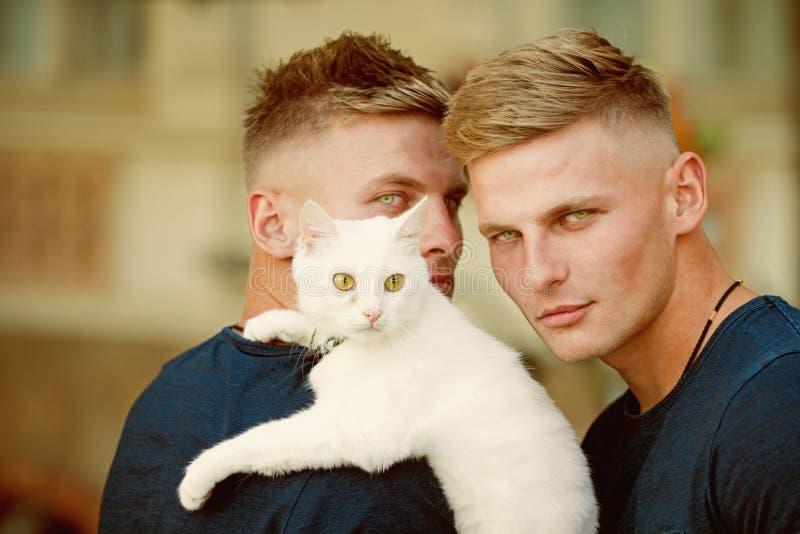 Zacht en warm omhels Spiermensen met leuke kat Gelukkige katteneigenaars op gang met huisdier De tweelingenmensen houden raskat g royalty-vrije stock afbeeldingen