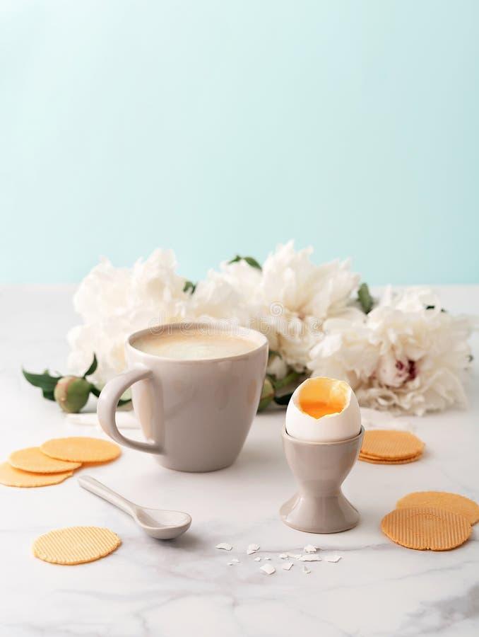 Zacht-gekookt ei met liquide oranje dooier in ceramisch eierdopje, kop van koffie en dunne knapperige graanspaanders op achtergro royalty-vrije stock foto's