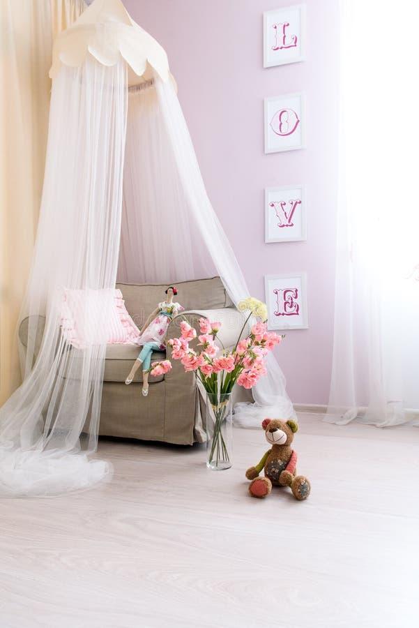 Zacht kleurde het roze ruimte, een comfortabele leunstoel met een luifel boven het stock foto
