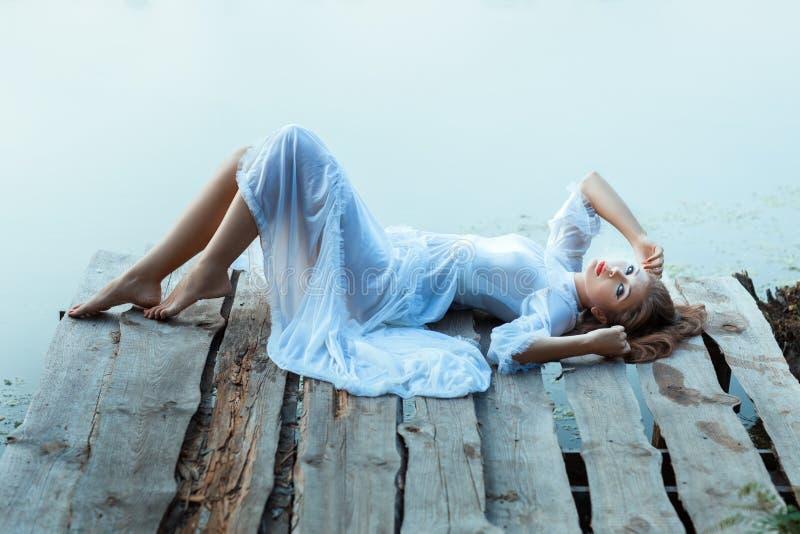 Zacht meisje in witte kleding die op een houten pijler liggen royalty-vrije stock afbeeldingen