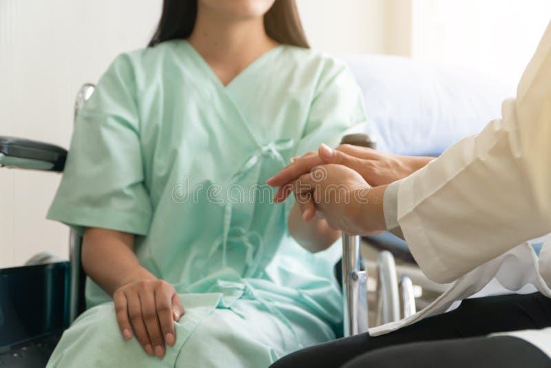 Zacht nadruk en onduidelijk beeld van geduldige zitting in rolstoel in het ziekenhuis En de arts houdt de hand van de patiënt om  stock afbeeldingen