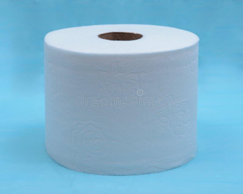 Zacht sterk en absorberend wit toiletpapier dat op blauw wordt geïsoleerd stock foto