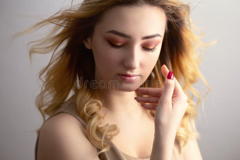Zacht studioportret van een mooie jonge vrouw, meisjesgezicht met krullend die haar van wind, het concept wordt verfomfaaid natuu royalty-vrije stock afbeeldingen