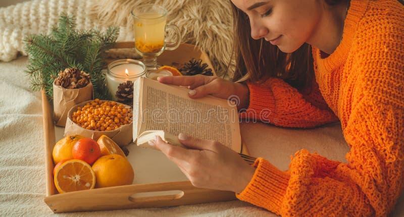 Zachte comfortabele foto van vrouw in warme oranje sweater op het bed met kop thee en fruit Meisjeszitting op het bed met oude bo royalty-vrije stock fotografie
