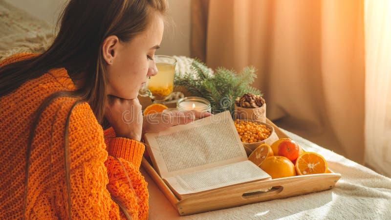 Zachte comfortabele foto van vrouw in warme oranje sweater op het bed met kop thee en fruit Meisjeszitting op het bed met oude bo stock afbeeldingen