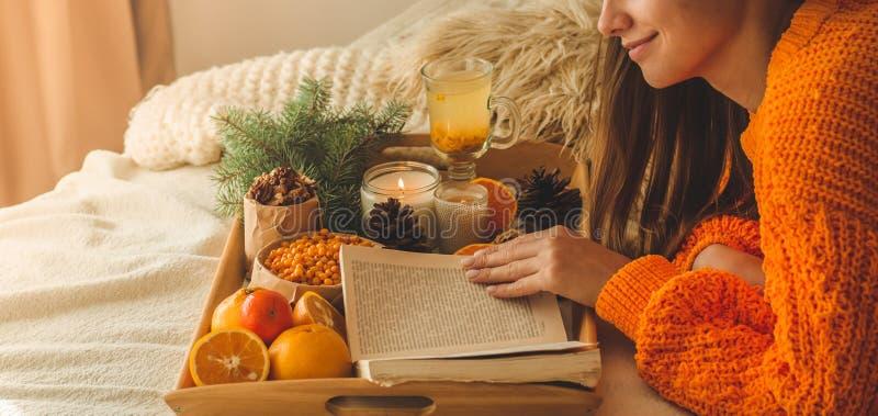 Zachte comfortabele foto van vrouw in warme oranje sweater op het bed met kop thee en fruit Meisjeszitting op het bed met oude bo stock foto
