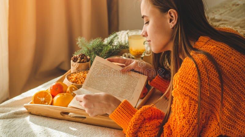 Zachte comfortabele foto van vrouw in warme oranje sweater op het bed met kop thee en fruit Meisjeszitting op het bed met oude bo royalty-vrije stock afbeeldingen