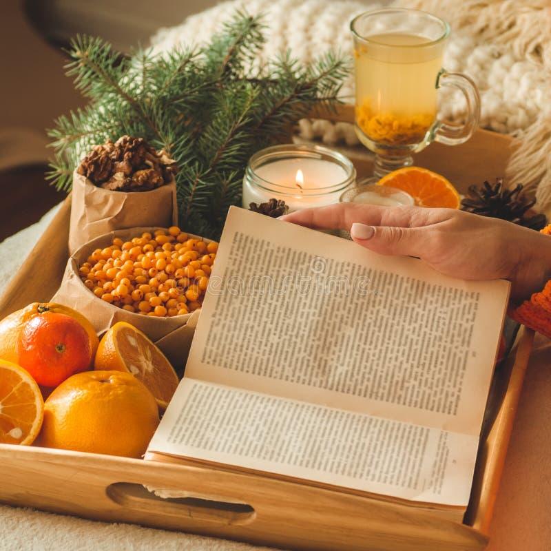 Zachte comfortabele foto van vrouw in warme oranje sweater op het bed met kop thee en fruit Meisjeszitting op het bed met oude bo stock fotografie