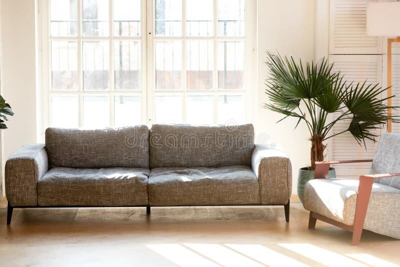 Zachte comfortabele grijze laag en leunstoel in woonkamer royalty-vrije stock foto's