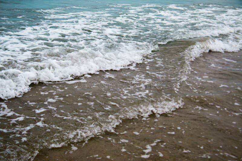 Zachte golf van blauwe oceaan op een zandig strand Met het onduidelijke beeld toning royalty-vrije stock fotografie