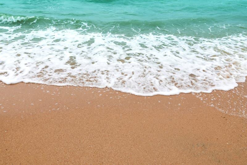 Zachte golf van blauwe oceaan op zandig strand stock afbeeldingen