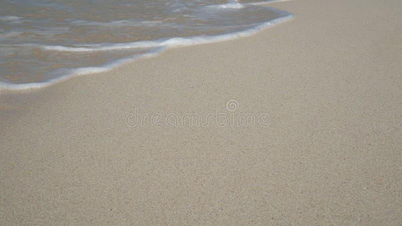 Zachte golf van blauwe oceaan op zandig wit strand De zomerachtergrond stock foto's