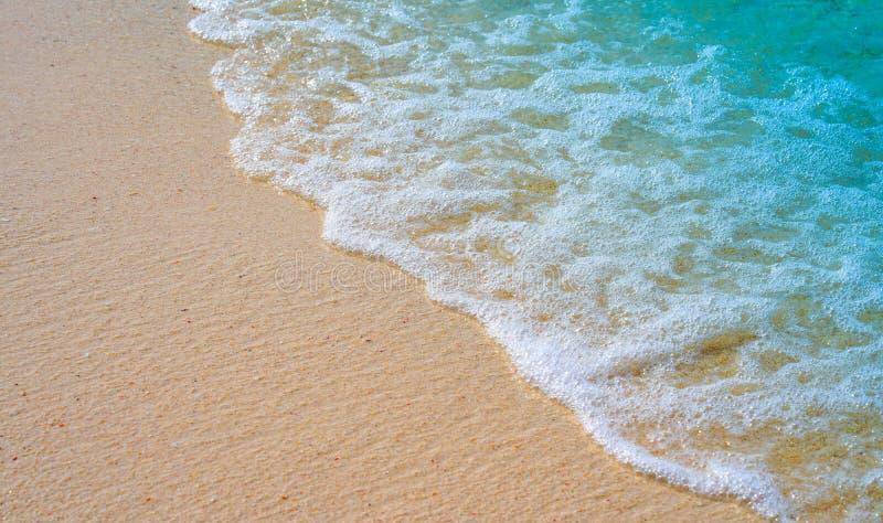 Zachte golf van blauwe oceaan op zandige strandachtergrond royalty-vrije stock foto