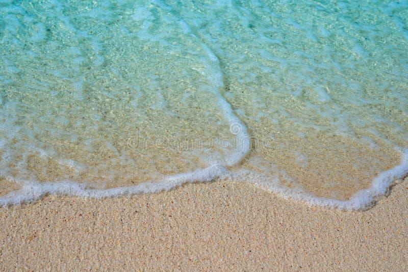 Zachte golf van blauwe oceaan op zandige strandachtergrond stock afbeeldingen