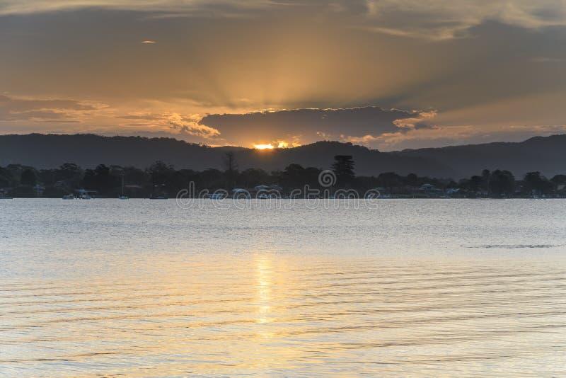 Zachte Gouden Zonsondergang over de Baai met Hoge Wolk stock afbeeldingen