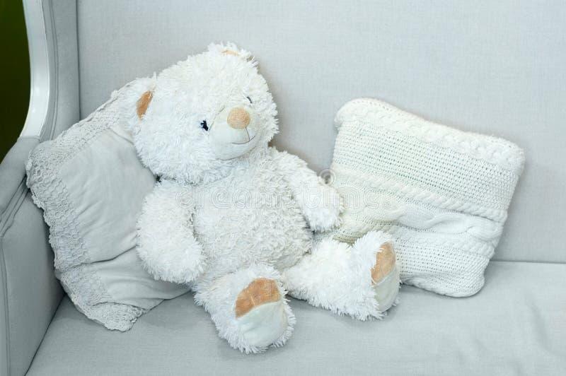Zachte grote stuk speelgoed ijsbeer Op laag met binnenlandse kussens stock fotografie