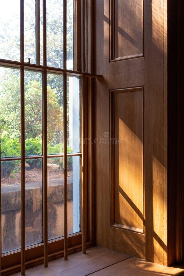Zachte lichte komst binnen door een diep venster met houten het met panelen bekleden en vensterbars, mening op tuin royalty-vrije stock foto's