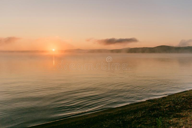 Zachte zachte lichtrose dageraad op het grote meer, Zonsopgang, rust, mist, horizonlijn royalty-vrije stock fotografie